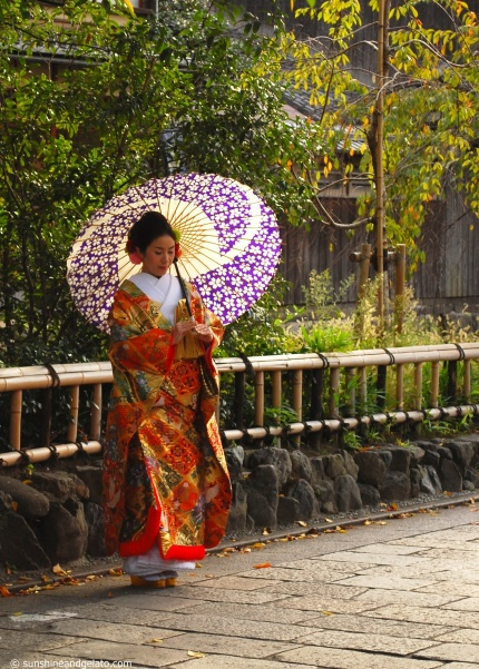 A bride in traditional kimono poses for photos.