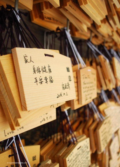 Ema (votive tablets) inside the Shrine complex. Shinto worshippers write wishes and prayers on these wooden plaques, and leave them hanging up at the Shrine where they believe the Shinto spirits will receive them.