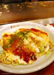The finished Hiroshima-style okonomiyaki, topped with bonito flakes.