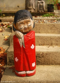 Wooden kokeshi doll sits on the steps outside a tea house on the Philosopher's Path.